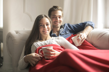 Sweet couple drinking hot tea, while lying down on the sofa under a red blanket