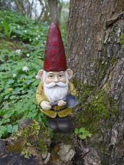 Gartenzwerg mit rotem Hut, gelber Jacke, braunen Stiefeln. Er hat eine Axt in der Hand und lehnt sich an einen alten Baumstamm.