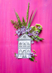 house made of paper and fresh flowers on pink wooden background
