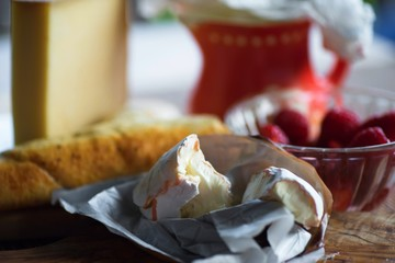 Camembert cheese, bowl with raspberry, bread and pitcher.