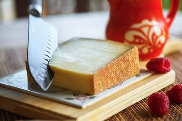 Gruyere cheese, knife, jug and raspberry.