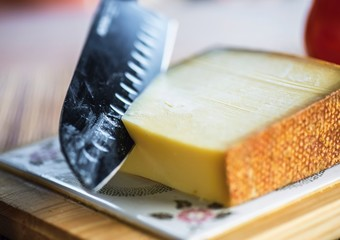 Knife slices gruyere cheese, closeup.