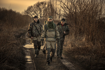 Group of men hunters with hunting equipment going on rural road hunting season sunset