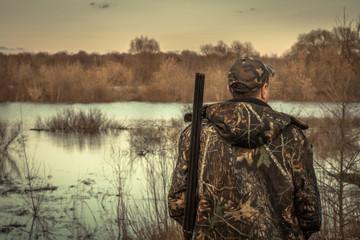 Hunter man shotgun camouflage exploring flood river hunting season rear view sunset