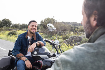 Handsome man sitting on motorbike and chatting with friend on remote road in countryside.
