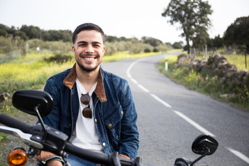 Handsome trendy man sitting on motorbike and smiling happily at camera on background of countryside.