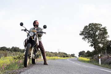 Adult man sitting on motorbike and looking away confidently with picturesque landscape in summertime on background.