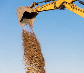 Excavator construction equipment unloading sand on blue sky background