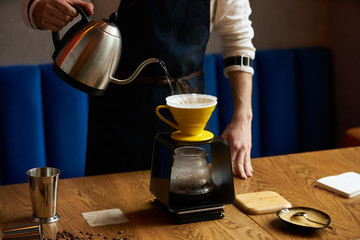 Bartender Hand drip coffee , Barista pouring water on coffee ground with paper filter