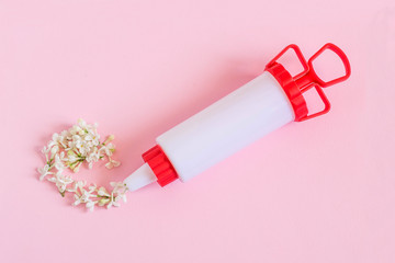 Creative idea: confectionery syringe and white lilac flowers instead of cream
