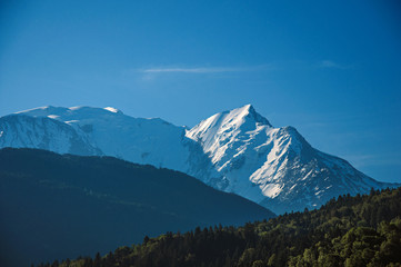 Alpine mountain landscape with forests and blue sky, near Saint-Gervais-Les-Bains. A famous ski resort located in Haute-Savoie Province, near the Mont Blanc in the French Alps.
