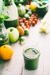 Green smoothie in bottle and  in  mason jars with apple,baby spinach, parsley and banana, on a wooden  board against a dark  background