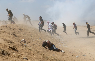 Palestinian demonstrator reacts as others run from tear gas fired by Israeli forces during a protest marking the 70th anniversary of Nakba, at the Israel-Gaza border in the southern Gaza Strip
