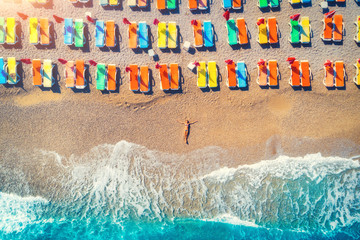 Aerial view of lying woman on the beach with colorful chaise-lounges. Young woman on the sea at sunset in Oludeniz, Turkey. Top view. Seascape with girl on the seashore, blue water and waves. Travel