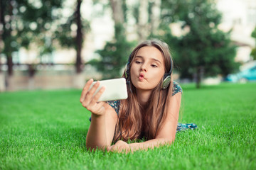 "Woman making a funny face known as a""fish-face"" puckering lips looking at phone"