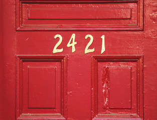 Red wooden door with gold numbers
