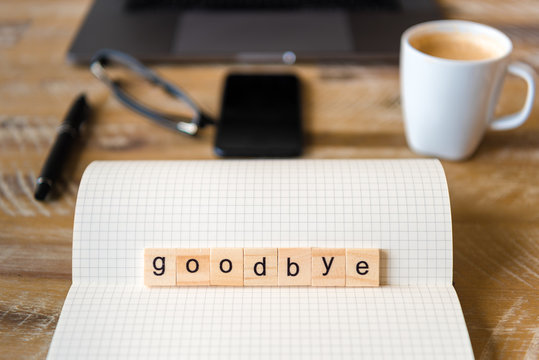 Closeup on notebook over wood table background, focus on wooden blocks with letters making Goodbye word