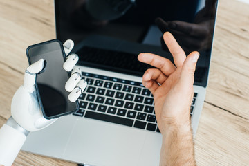 cropped shot of human and robot hands using smartphone and laptop with blank screens