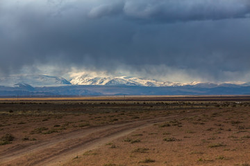 Foto op Canvas Donkergrijs Road through the steppe and mountains of Western Mongolia in bad weather.