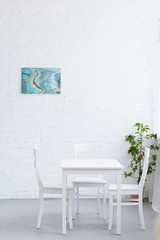 empty table in light cozy apartment with abstract painting on wall