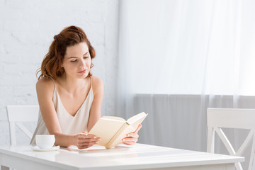focused young woman reading book with coffee cup on table at home