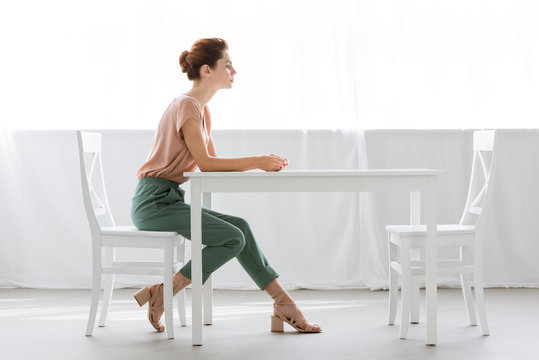 side view of attractive young woman sitting at table alone at home