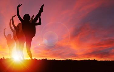 Silhouette Girls Dancing at Golden Sunrise