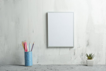Empty white frame with a flower with pencils against the wall background. The concept of design and font inscriptions and image placement