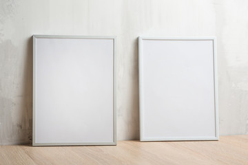 Two white frames on the wall background. The concept of design and font inscriptions and image placement