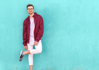 fashion guy in glasses poses near the wall the color of the sour wave