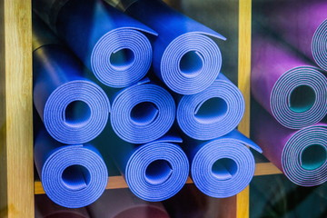 Close up image of yoga mats for sale through a shop window