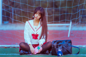 A girl sitting in front of a football net