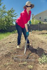Gardening. Female with rake working on yard. Closeup.