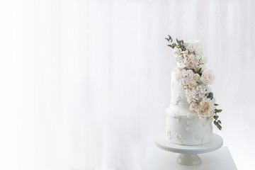 White tiered wedding cake with edible bouquet of flowers wrapped around it. (Left)