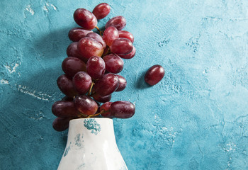 red grapes on a blue background, grapes bunches