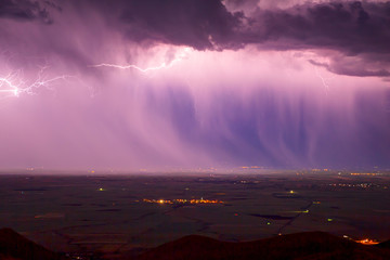 Lightning storm over city with rain in purple light