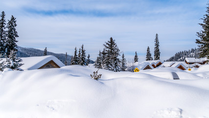 Wall Mural - Deep snow pack covering houses and roads of the alpine village of Sun Peaks in the Shuswap Highlands of central British Columbia, Canada
