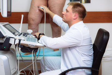 Doctor in a white coat with a clinic with diagnostic equipment. Surgeon man performs an ultrasound using a device on the legs of a female patient. Medical tools in hospital.