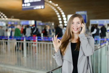 Businesswomna talking by smartphone at airport hall, wearing grey coat and black bag, showing ok. Concept of speaking with close people and traveling abroad, positive emotions.