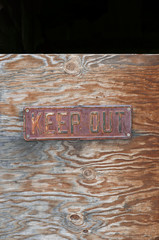 """Metal sign with the words """"Keep out"""" on a wooden background"""