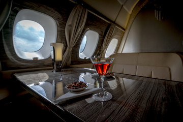 Interior of a business class of a commercial passenger plane, an armchair and a window, a table and a cocktail glass with a drink.