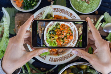 Smartphone photography of food for lunch or dinner. Woman hands takes phone photo of food for social media and blogging publications. Raw vegan vegetarian healthy food