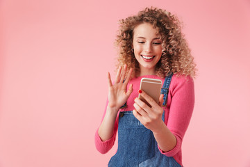 Portrait of happy young girl with curly hair waving