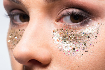 attractive woman with glitter under eyes looking at camera