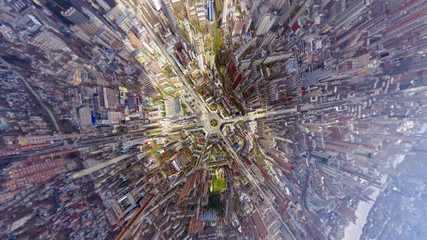 Helicopter drone shot. Aerial photography of a modern city over an area, a large crossroads, high-rise buildings, a park and roads. Panoramic city shot from above