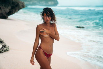 Gorgeous young woman in a red bikini without bra on a white sand beach, covering her breast with hand. Summer vacation girl on the island. Model tans and poses near the ocean.