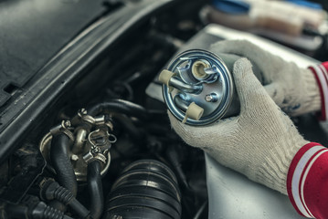 An auto mechanic replaces a car's fuel filter.