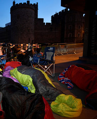 Royal fans sleep on the pavement outside Windsor Castle, the location for the forthcoming wedding of Britain's Prince Harry and his fiancee Meghan Markle, in Windsor