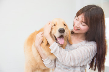 Asian beautiful woman playing with her dog and smiles at home