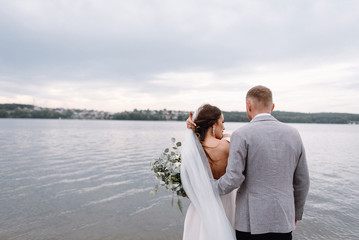 An amazing couple on their wedding day near the lake hug and enjoy each other. The bride and groom with a bouquet are happy together